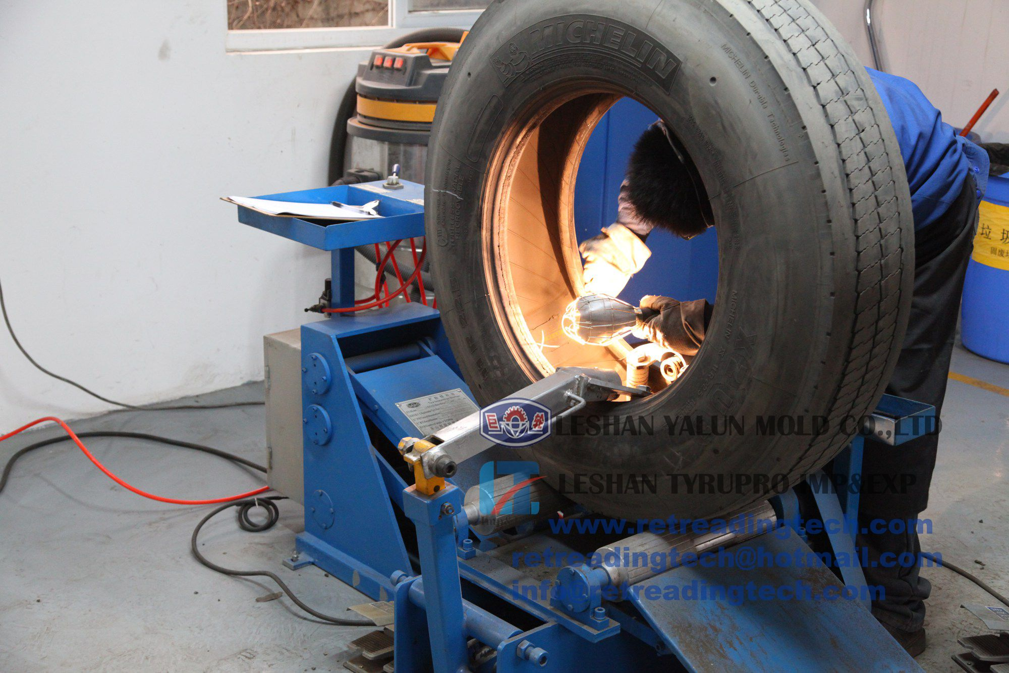 a worker using a truck/bus tire inspection spreader in a tire retreading factory